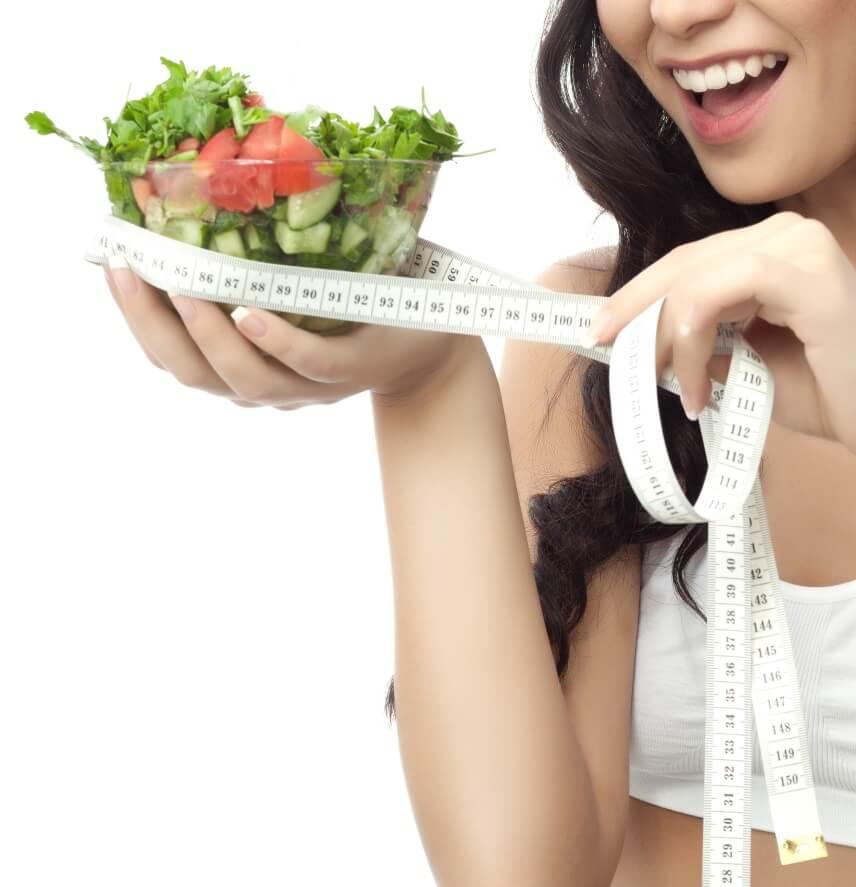 Mulher segurando uma salada e uma fita métrica